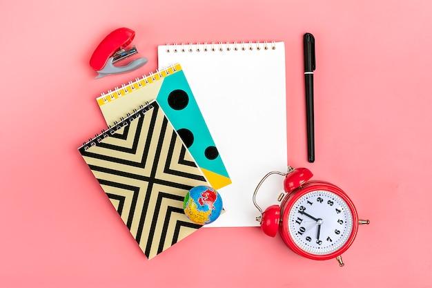 Powrót do koncepcji szkoły. przybory szkolne na różowo, płasko.