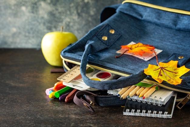 Powrót do koncepcji szkoły przybory szkolne z niebieskim plecakiem na stole wolne miejsce na tekst