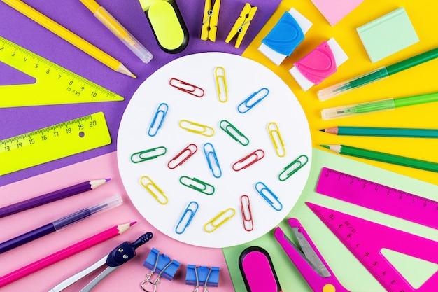 Powrót do koncepcji szkoły różne narzędzia do pisania i inne stacjonarne szkoły na kolorowym tle papieru