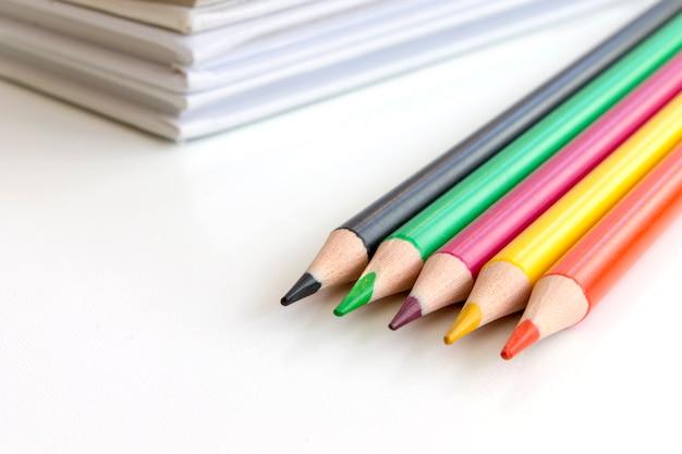 Powrót do koncepcji szkoły. stubarwni ołówki z książkami na tle.