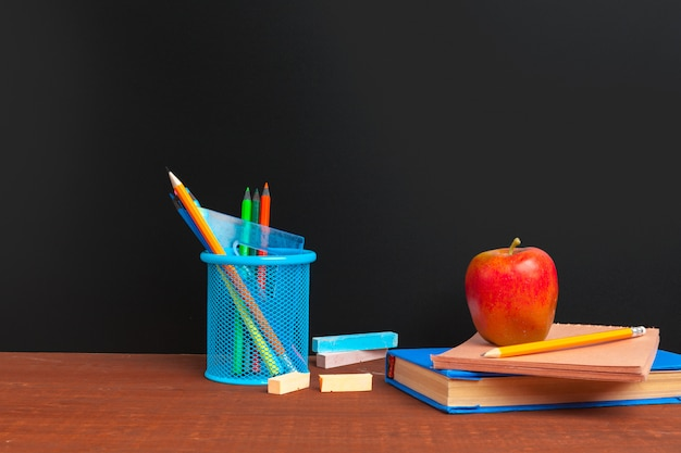 Powrót do koncepcji szkoły. tablica z książkami i jabłkiem na drewnianym biurku
