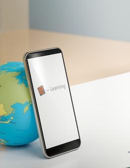 Powrót do koncepcji szkoły, telefon komórkowy na białym stole z globusem świata, edukacja online, renderowanie 3d