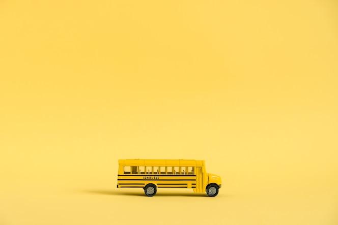 Powrót do koncepcji szkoły. tradycyjny żółty autobus szkolny na żółtym tle