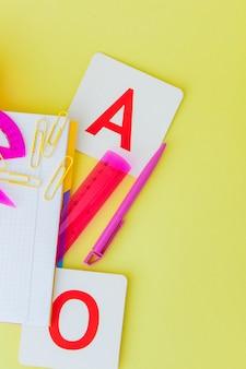Powrót do koncepcji szkoły z miejsca na tekst. widok z góry. skopiuj miejsce szkolne artykuły biurowe. kreatywne biurko z kolorowymi artykułami. kolorowy spinacz do papieru. artykuły szkolne na żółtym tle. biurko