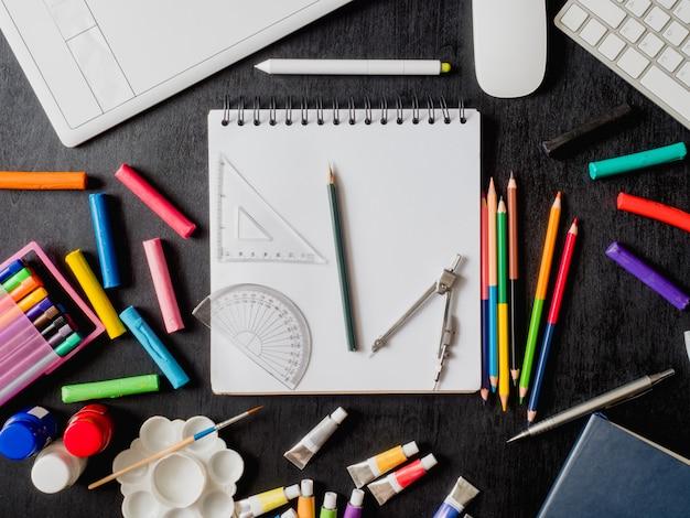 Powrót do koncepcji szkoły z rysunkiem, kredkami, kredkami, kolorem plakatu, tabletem graficznym, klawiaturą, myszą i papeterią szkolną na czarnym tle drewnianych z miejsca kopiowania