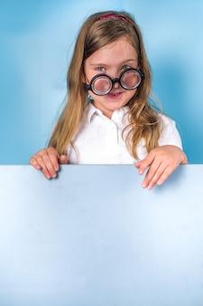 Powrót do koncepcji szkoły. zaproszenie do szkoły, baner reklamowy. śliczna uczennica szkoły podstawowej w biało-niebieskim klasycznym mundurze, śmieszne okulary. kolorowa, jasnoniebieska, modna przestrzeń do kopiowania w tle copy