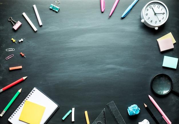 Powrót do przyborów szkolnych i akcesoriów biurowych na tle tablicy. projekt widoku z góry