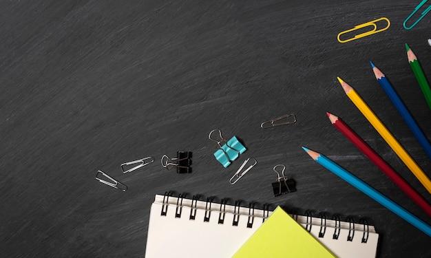 Powrót do szkoły. akcesoria, książki i kredki na tle tablicy. widok z góry.