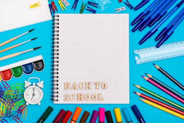 Powrót do szkoły. artykuły papiernicze, budzik i napis drewnianymi literami w zeszycie na niebieskim tle. widok z góry