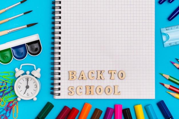 Powrót do szkoły. artykuły papiernicze, budzik i napis drewnianymi literami w zeszycie na niebieskim tle
