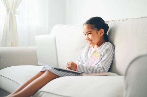 Powrót do szkoły, azjatycka dziewczynka za pomocą swojego laptopa