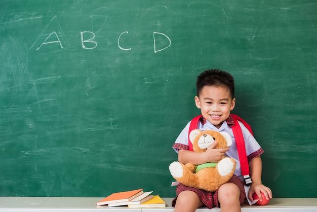 Powrót do szkoły azjatycki śliczny mały chłopiec z przedszkola w mundurku studenckim z uśmiechniętą torbą szkolną