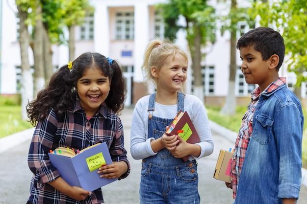 Powrót do szkoły. bliska trzech przyjaciół z plecakami przytulanie i śmiejąc się przed szkołą. mieszana grupa rasowa dzieci w szkole bawiących się na szkolnym boisku.