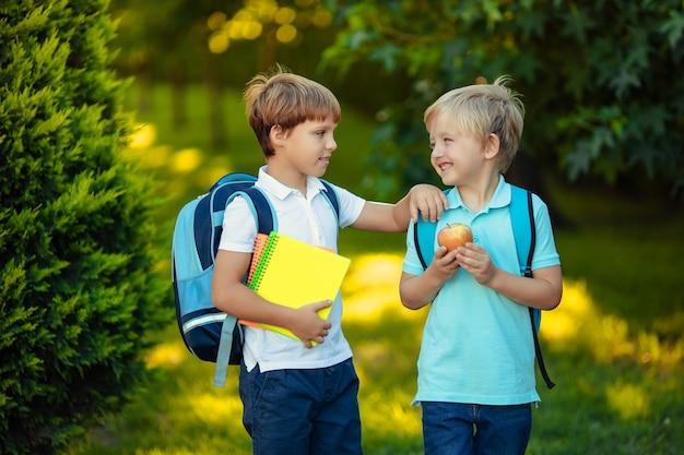 Powrót do szkoły. dwa szczęśliwe wesołe dzieci z plecakami i zeszytami w rękach w parku.