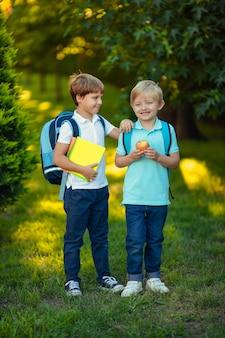 Powrót do szkoły. dwa szczęśliwe wesoły chłopiec dzieci z plecakami i zeszytami w rękach w parku.