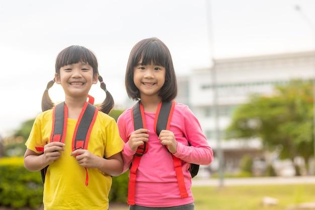Powrót do szkoły. dwie śliczne azjatyckie dziewczynki ze szkolną torbą, trzymające razem książkę w szkole