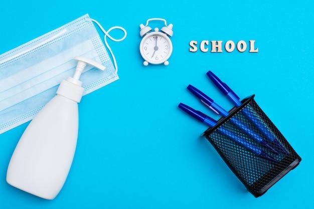 Powrót do szkoły. dystans społeczny. budzik, drewniane litery, długopisy w pojemniku, maska ochronna i środek dezynfekujący na niebieskim tle