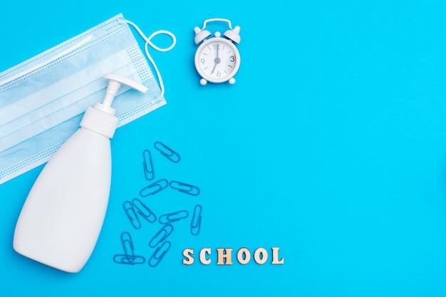 Powrót do szkoły. dystans społeczny. budzik, drewniane litery, maska ochronna i środek dezynfekujący na niebieskim tle