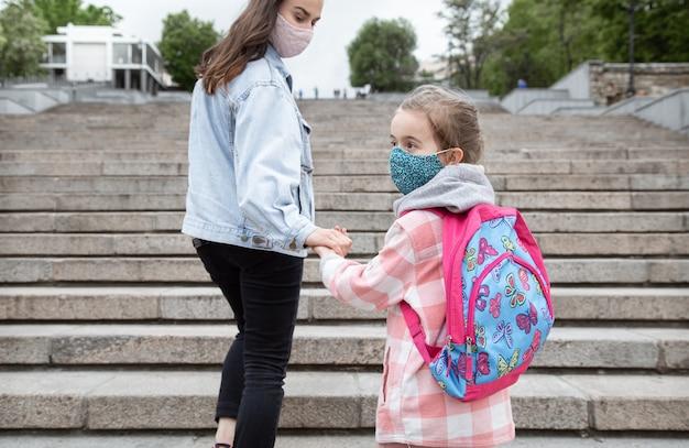 Powrót do szkoły. dzieci z pandemią koronawirusa chodzą do szkoły w maskach. matka trzymając się za ręce z dzieckiem