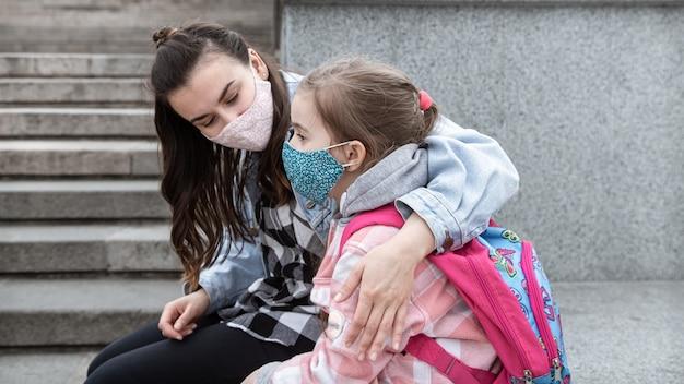 Powrót do szkoły. dzieci z pandemią koronawirusa chodzą do szkoły w maskach. przyjazne relacje z matką. edukacja dzieci.