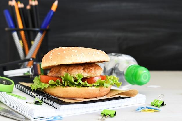 Powrót do szkoły. edukacja kwarantannowa. pudełko na lunch z hamburgerami, wodą i akcesoriami szkolnymi na tle tablicy szkolnej.