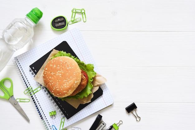 Powrót do szkoły. edukacja kwarantannowa. pudełko na lunch z hamburgerem, wodą i akcesoriami szkolnymi