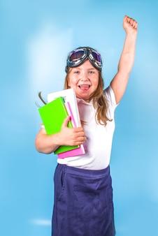 Powrót do szkoły, inspiracja edukacyjna dla dzieci w nauczaniu przedmiotów ścisłych, dążenie do wiedzy. urocza uczennica podstawowa w biało-niebieskim mundurku, z latającymi goglami, skacząca na kolorowym niebieskim tle