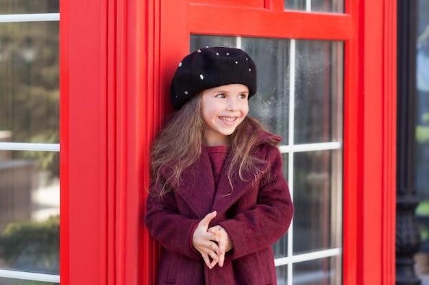 Powrót do szkoły, jesień. mała uśmiechnięta dziewczyna w czerwonym płaszczu i berecie stoi przy angielskiej czerwonej budce telefonicznej. londyn, anglia, wielka brytania. europa cel podróży. stara szkoła. edukacja