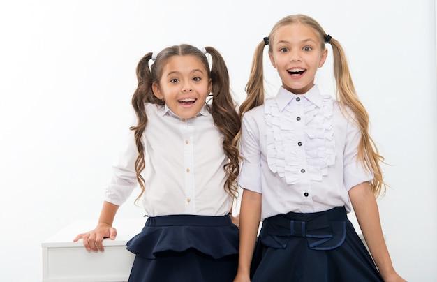 Powrót do szkoły jest tutaj. małe dziewczynki chętnie wracają do szkoły. szczęśliwe dziewczynki.