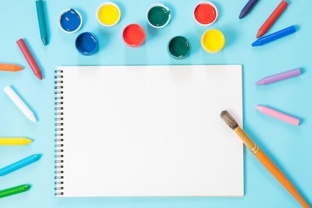 Powrót do szkoły. kolorowe farby, album i pędzel na mocnym błękicie. skopiuj miejsce. widok z góry.
