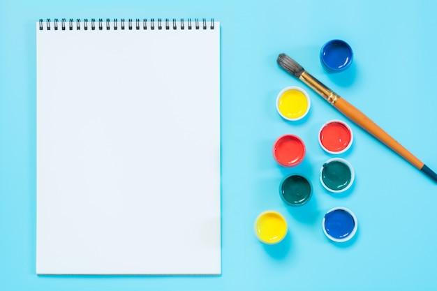 Powrót do szkoły. kolorowe farby, album i pędzel na wyrazistym błękicie. skopiuj miejsce