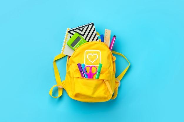 Powrót do szkoły, koncepcja edukacji. żółty plecak z przyborów szkolnych - notatnik, długopisy, linijka, kalkulator, nożyczki na białym tle na niebieskim tle. widok z góry.