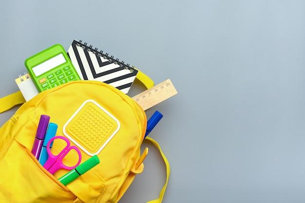 Powrót do szkoły, koncepcja edukacji. żółty plecak z przyborów szkolnych - notatnik, długopisy, linijka, kalkulator, nożyczki na białym tle na szarym tle. widok z góry.