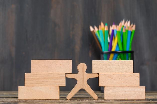 Powrót do szkoły koncepcja z drewnianymi klockami, ludzką postacią, ołówkami na drewnianym stole widok z boku.