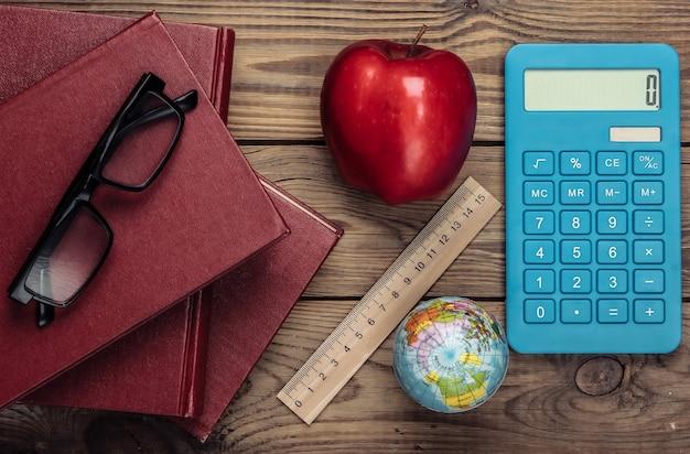 Powrót do szkoły. książki, linijka, kula ziemska, kalkulator, czerwone jabłko na drewnianym stole