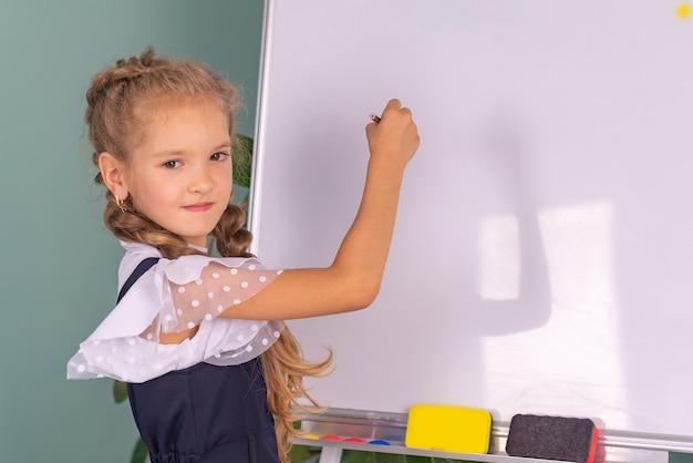 Powrót do szkoły ładna dziewczyna w szkole z książkami w pobliżu tablicy