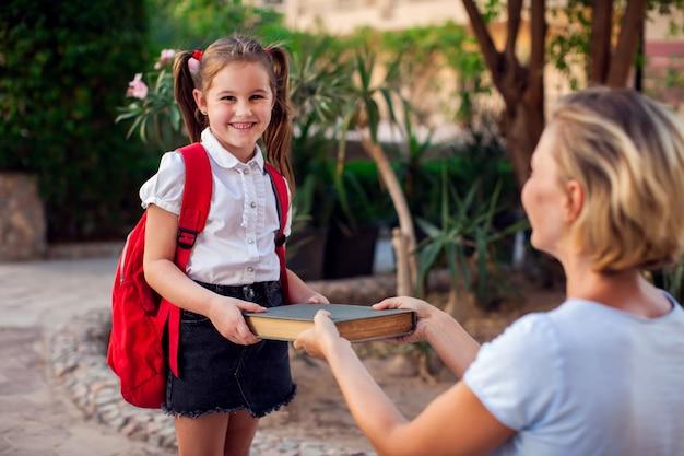 Powrót do szkoły. matka daje książkę dziecku przed pójściem do szkoły