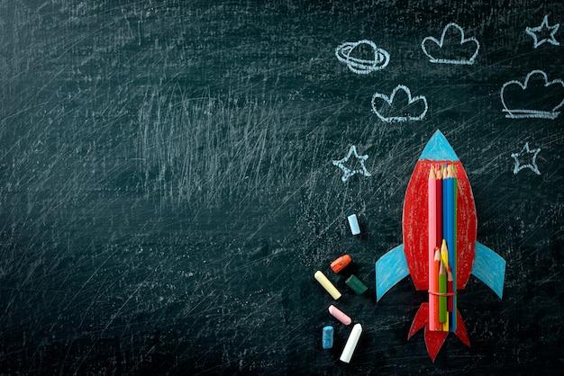 Powrót do szkoły. odgórny widok malująca papier rakieta na chalkboard tle