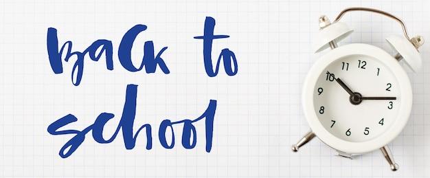 Powrót do szkoły. odręczny napis i budzik na białym papierze w kratkę