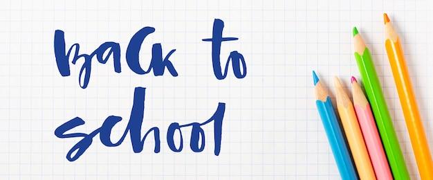 Powrót do szkoły. odręczny napis. przybory szkolne na białym papierze w kratkę.