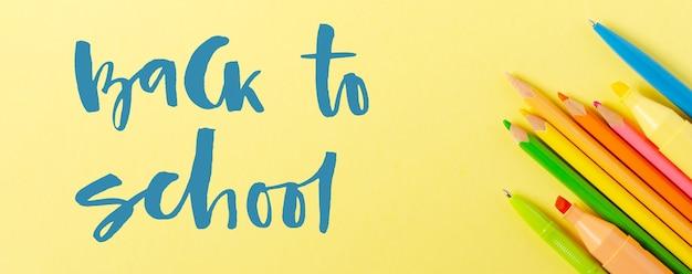 Powrót do szkoły. odręczny napis. przybory szkolne na żółtym tle papieru.