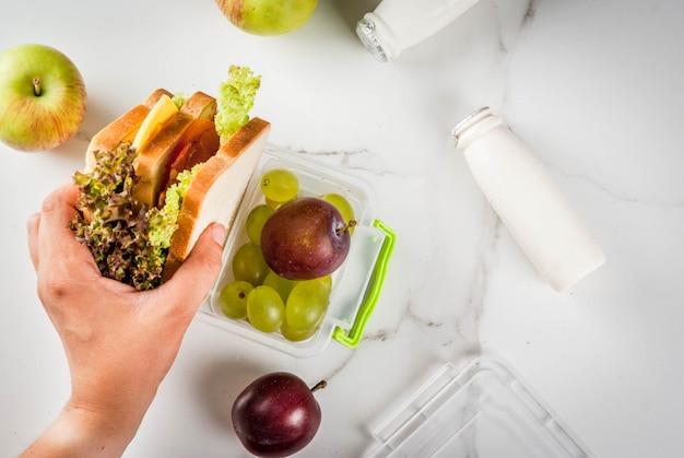 Powrót do szkoły. osoba wytwarzająca zdrowe pudełko na lunch ze świeżymi owocowymi jabłkami, śliwkami, winogronami, jogurtem, sałatą kanapkową, pomidorami, serem, mięsem. stół z białego marmuru. widok z góry kobiece ręce