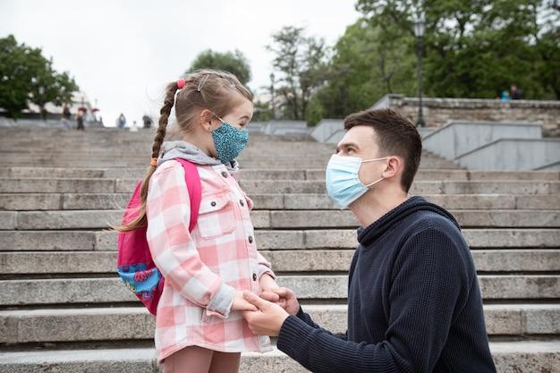 Powrót do szkoły, pandemia. młody ojciec i córeczka w masce. przyjazne relacje rodzinne.
