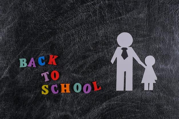 Powrót do szkoły. papierowy ojciec z córką na tablicy kredowej z tekstem z powrotem do szkoły