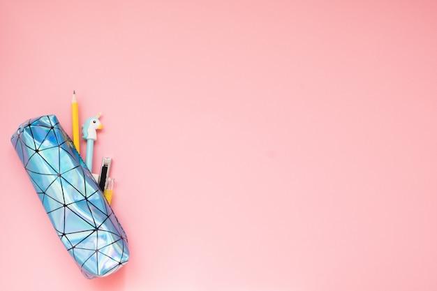 Powrót do szkoły. piórnik z przyborów szkolnych na różowym stole