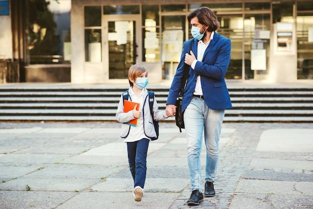 Powrót do szkoły podczas pandemii koronawirusa. ojciec zabiera syna do szkoły.