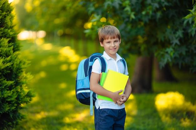 Powrót do szkoły. portret szczęśliwy uśmiechnięty chłopiec dziecko z książkami w ręce w parku.