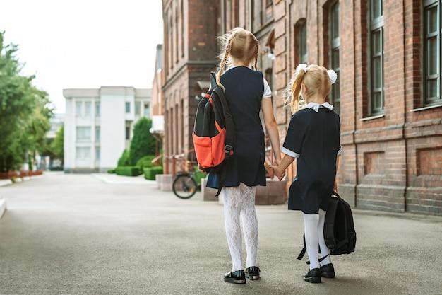 Powrót do szkoły, portret z tyłu uczniów szkół podstawowych z plecakami