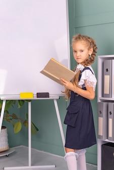 Powrót do szkoły pracowite dziecko siedzi przy stole w pomieszczeniu dziewczyna czyta książkę