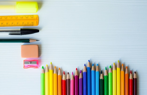 Powrót do szkoły ramki z tęczy kolorowych piór i innych przyborów szkolnych i białe drewniane tła